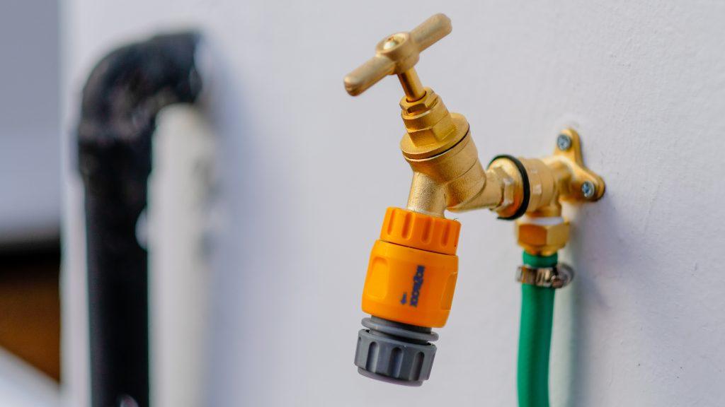 Un robinet relié à un tuyau d'arrosage vert