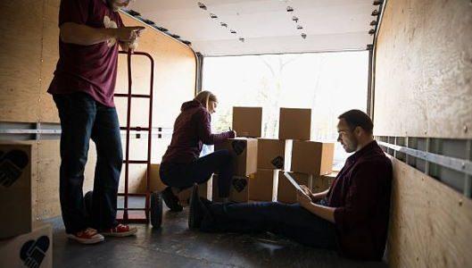 Groupe de personnes qui utilisent leur smartphone lors d'un déménagement