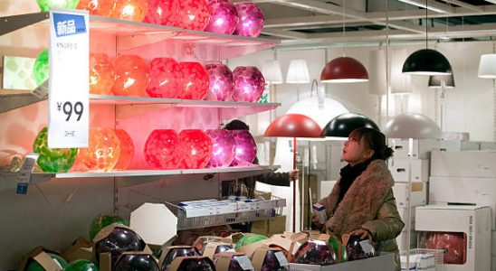 Jeune femme qui choisit une lampe dans un magasin de luminaires