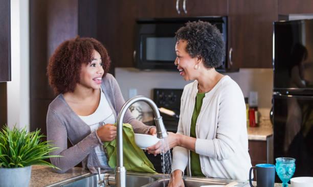 Jeune aide-ménagère qui aide une femme âgée à faire la vaisselle