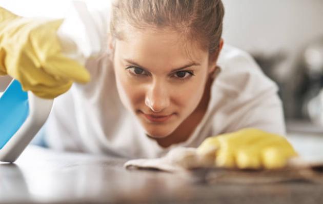 Femme de ménage qui nettoie un plan de travail avec des gants en silicone et un chiffon