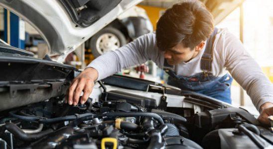 Garagiste qui inspecte le moteur d'une voiture lors de la révision