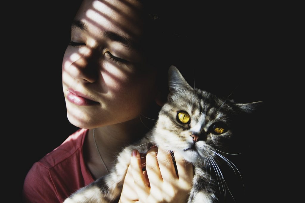 Femme qui tient un chat dans ses bras et lui fait un câlin