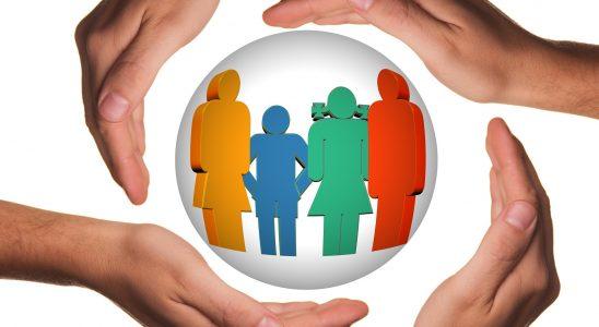 Quatre mains qui entourent 4 membres d'une famille représentés sous la forme de bonhommes de couleurs différentes dans une bulle
